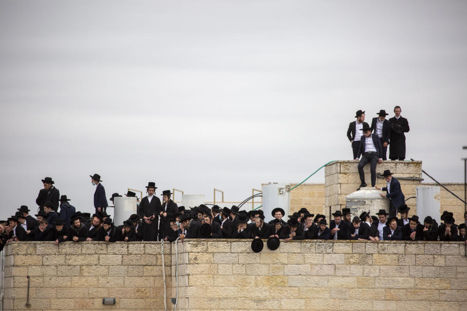Ultra-Orthodox Jews participate in the funeral for prominent rabbi Meshulam Soloveitchik, in Jerusalem, Sunday, Jan. 31, 2021. The mass ceremony took place despite the country's health regulations banning large public gatherings, during a nationwide lockdown to curb the spread of the coronavirus. (AP Photo/Ariel Schalit)