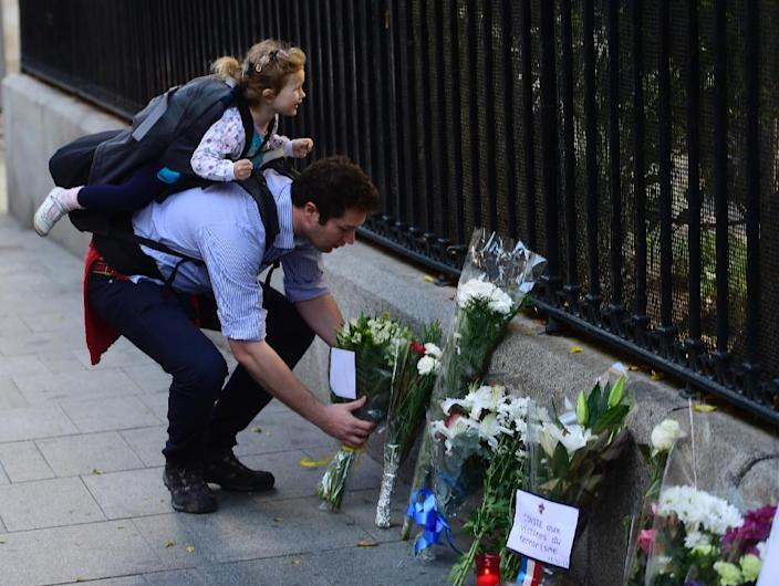 A man places flowers outside the French Embassy in Madrid on November 14, 2015 (AFP Photo/PIERRE-PHILIPPE MARCOU)