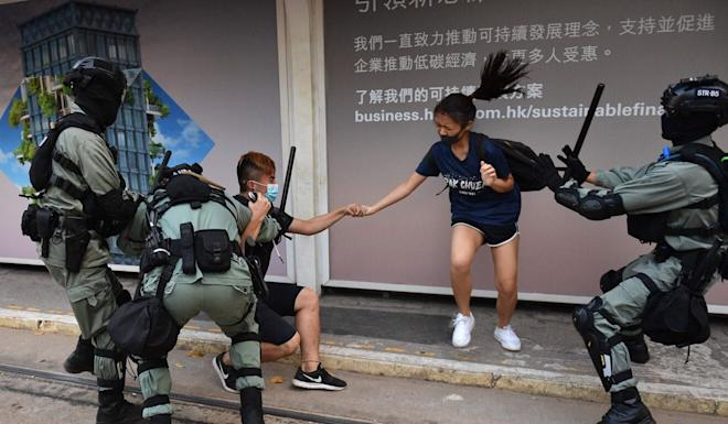 Hong Kong police chase down a couple wearing face masks in Hong Kong's Central district on October 5, a day after the city's leader outlawed face coverings. Photo: AFP