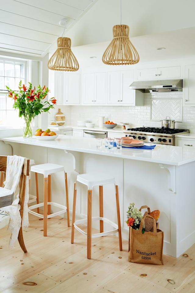 <p>Let a small space gleam by incorporating buckets and buckets of white paint. Here, white walls, rafters, cabinetry, backsplash, and countertops come together in an airy kitchen that belies its small square-footage. A few wooden and wicker elements, such as the pendant lights, cutting board, and oak floating, keep the look from going sterile.</p>