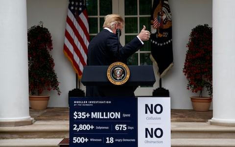 Democrats pointed to the pre-printed poster about Robert Mueller's probe as proof that Donald Trump's rebuke was planned and not 'spontaneous' - Credit: AP Photo/Evan Vucci