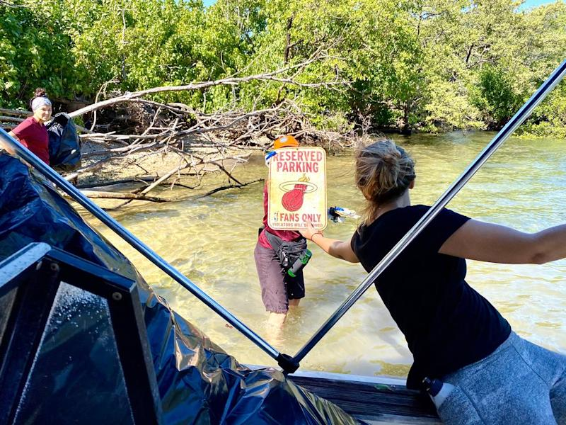 A discarded parking sign for a Miami Heat fan somehow made its way to Bird Key in Biscayne Bay. It was found by volunteers among decades of trash on the island.