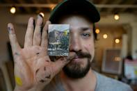 Artist Steve Wasterval poses with a mini painting in his studio in Greenpoint, in Brooklyn, New York, on May 25, 2021. He will hide it in the neighborhood for people to find