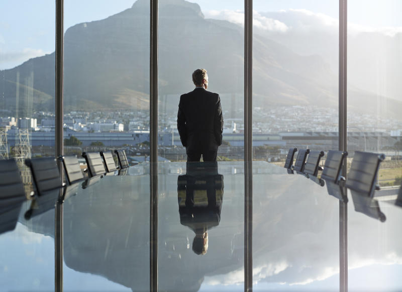 Portrait of male CEO in big corner office, looking out of window, at sunset