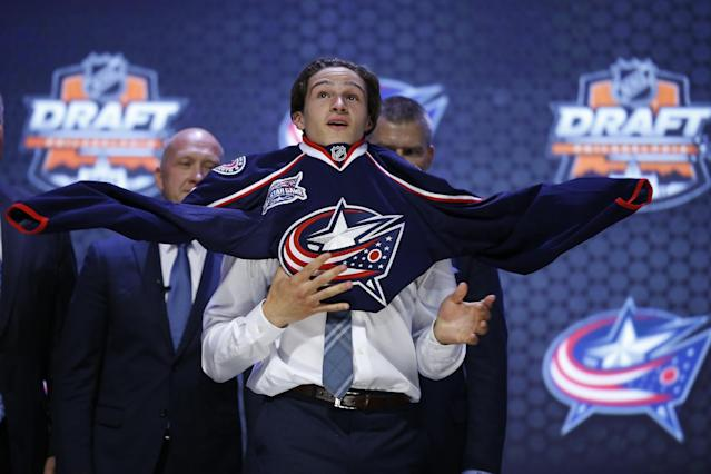 Sonny Milano pulls on a Columbus Blue Jackets sweater after being chosen 16th overall during the first round of the NHL hockey draft, Friday, June 27, 2014, in Philadelphia. (AP Photo/Matt Slocum)