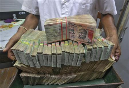 An employee poses with the bundles of Indian rupee notes inside a bank in Agartala, the capital of India's northeastern state of Tripura August 22, 2013.
