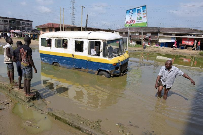 A bus breaks down on the flooded Port Harcourt-Aba highway, abandoned by maintenance agencies (AFP Photo/Pius Utomi Ekpei)