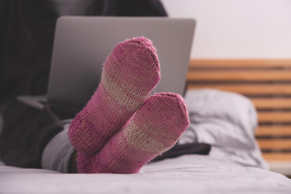 Close up image of pink, purple cozy soft warm knitted winter socks on woman's legs. The unrecognizable woman lying in bed, using a laptop.