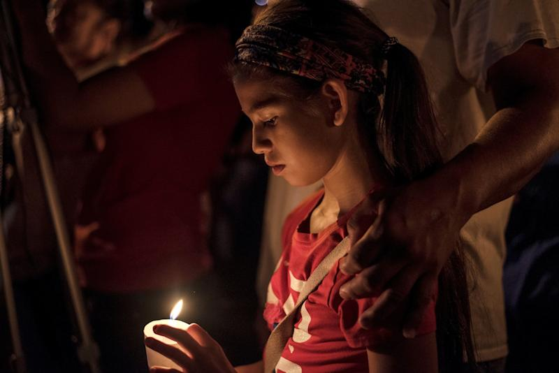 Sofia Martinez, 9, attends a candlelight vigil after a mass shooting at the First Baptist Church.