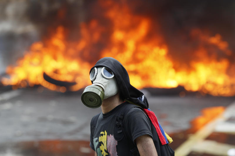 An anti-government protester stands in front of burning barricade on a highway in Caracas, Venezuela, Monday, April 24, 2017. Thousands of protesters shut down the capital city's main highway to express their disgust with the socialist administration of President Nicolas Maduro. Protesters in least a dozen other cities also staged sit-ins as the protest movement is entering its fourth week. (AP Photo/Ariana Cubillos)