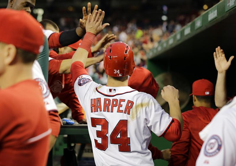 Washington Nationals left fielder Bryce Harper (34) celebrates with his teammates after he scored on an RBI single by Jayson Werth during the fourth inning of a baseball game against the Cincinnati Reds at Nationals Park Friday, April 26, 2013, in Washington. (AP Photo/Alex Brandon)
