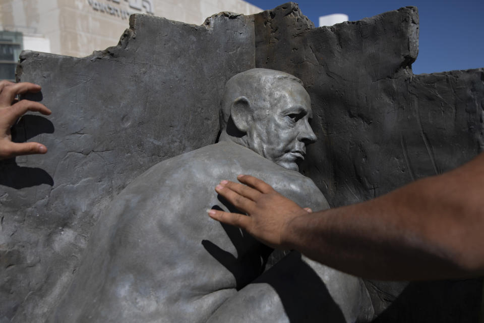 Municipal workers remove a statue created by an unidentified artist depicting a naked Prime Minister Benjamin Netanyahu, in Habima Square in Tel Aviv, Israel, Wednesday, March 17, 2021. The sculpture sat at the site for a few hours before being removed. Israel is holding its fourth election in less than two years on March 23. (AP Photo/Oded Balilty)