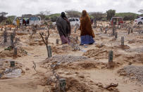 FILE - In this May, 13, 2020, file photo, women walk past graves at a cemetery in Mogadishu, Somalia, following the burial of a man who died of COVID-19. Africa has surpassed 100,000 confirmed deaths from COVID-19 as the continent praised for its early response to the pandemic now struggles with a dangerous resurgence and medical oxygen often runs desperately short. (AP Photo/Farah Abdi Warsameh, File)