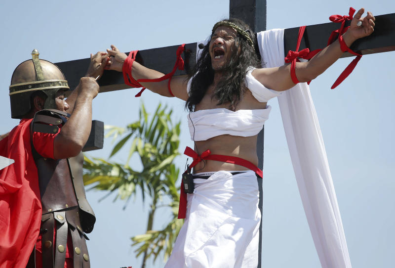 Filipino penitent Ruben Enaje, who has portrayed as Jesus Christ for 27 times, reacts as a nail is removed from his hand after being crucified during Good Friday rituals on March 29, 2013 at Cutud, Pampanga province, northern Philippines. Several Filipino devotees had themselves nailed to crosses Friday to remember Jesus Christ's suffering and death, an annual rite rejected by church leaders in this predominantly Roman Catholic country. (AP Photo/Aaron Favila)