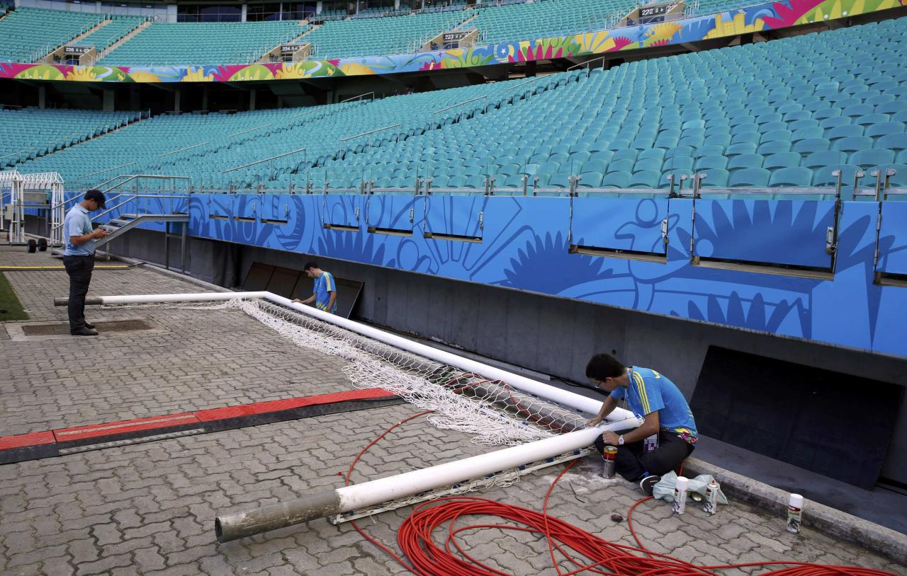 Volunteers work on the goal post inside the Arena Fonte Nova stadium ahead of the 2014 World Cup in Salvador, June 12, 2014. REUTERS/Marcos Brindicci (BRAZIL - Tags: BUSINESS CONSTRUCTION SOCCER SPORT WORLD CUP)