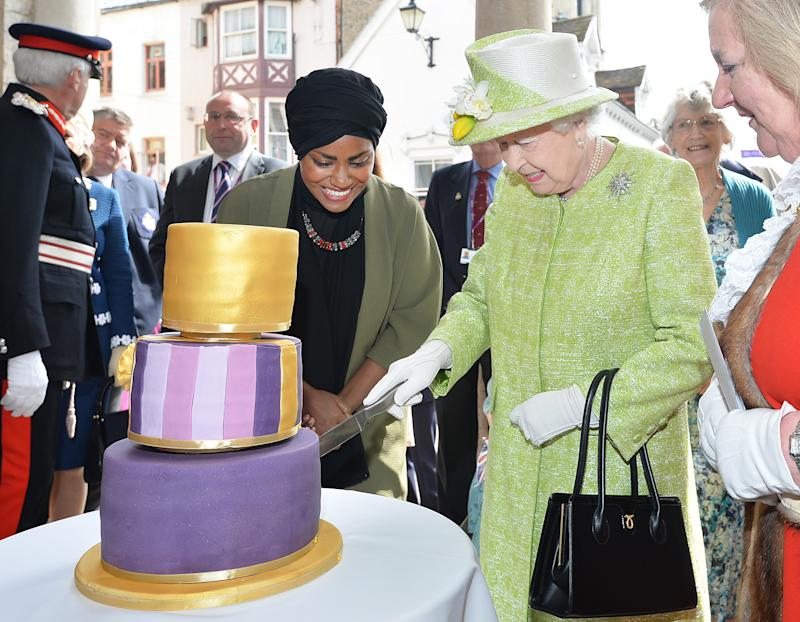 Britain's Queen Elizabeth II cuts into a cake made by Nadiya Hussein (L), winner of the Great British Bake Off during a 'walkabout' on her 90th birthday in Windsor, west of London, on April 21, 2016. Britain celebrates Queen Elizabeth II's 90th birthday on Thursday, with her eldest son Prince Charles paying tribute in a special radio broadcast and Prime Minister David Cameron leading a parliamentary homage. / AFP / POOL / John Stillwell (Photo credit should read JOHN STILLWELL/AFP via Getty Images)