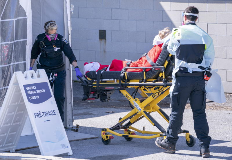 A patient is wheeled into the emergency unit of the Verdun Hospital in Montreal on Monday, April 6, 2020. Prime Minister Justin Trudeau says he's confident Canada will still be able to import N95 protective masks form the U.S. despite an export ban and says he will talk to U.S. President Donald Trump in the coming days. (Paul Chiasson/The Canadian Press via AP)