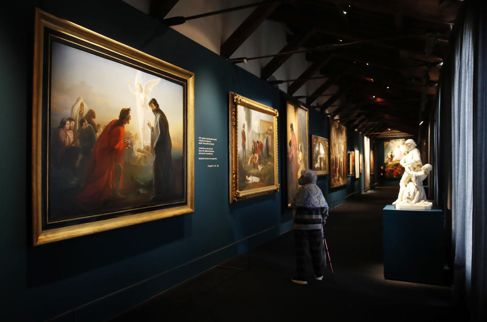 """A woman looks at paintings at the """"Dante. La visione dell'arte"""" (Dante. The Vision of Art) exhibition, in Forli, Italy, Saturday, May 8, 2021. Italy is honoring its great poet Dante Alighieri in myriad ways on the 700th anniversary of his death, with new musical scores and gala concerts, exhibits and dramatic readings against stunning backgrounds in every corner of the land. (AP Photo/Antonio Calanni)"""