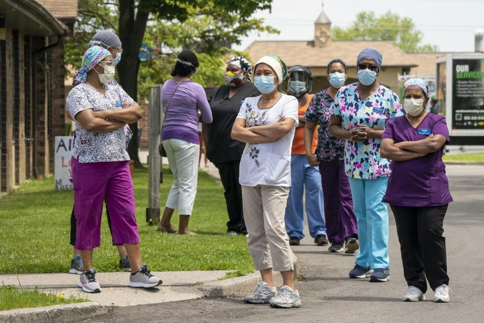 Workers wearing masks stand in a group outside a long-term care home.