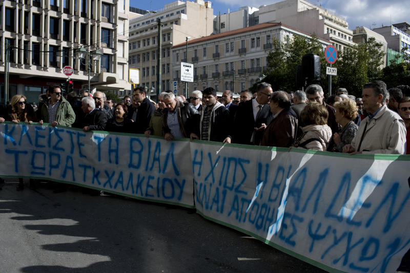 """Residents and Mayors of the island of Lesvos, Chios , and Samos hold a banner as they protest outside the Migration Ministry in central Athens, Tuesday, Dec. 5, 2017. The protesters demonstrated against the increasingly precarious and overcrowded conditions for newly arriving migrants and refugees. The banner reads in Greek """" island of Chios is not human warehouse"""" (AP Photo/Petros Giannakouris)"""