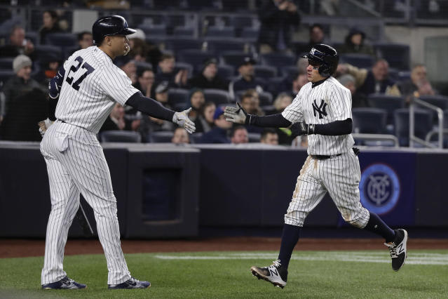 New York Yankees' Ronald Torreyes, right, is congratulated by Giancarlo Stanton after Torreyes scored on a base hit by Didi Gregorius during the fifth inning of a baseball game against the Toronto Blue Jays, Thursday, April 19, 2018, in New York. (AP Photo/Julie Jacobson)