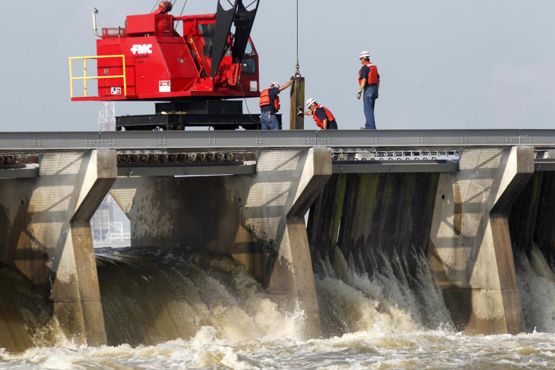 Workers use cranes to remove some of the Bonnet Carre Spillway's wooden barriers, which serve as a dam against the high water in Norco, La., Monday, May 9, 2011 in anticipation of rising floodwater. The spillway, which the Corps built about 30 miles upriver from New Orleans in response to the great flood of 1927, last opened during the spring 2008. Monday marked the 10th time it has been opened since the structure was completed in 1931. The spillway diverts water from the Mississippi River to Lake Pontchartrain. (AP Photo/Gerald Herbert)