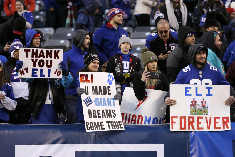 File-This Dec. 15, 2019, file photo shows New York Giants fans holding signs for Giants quarterback Eli Manning after an NFL football game against the Miami Dolphins, in East Rutherford, N.J. The man who has been the face of the New York Giants since 2004 is probably going to make his final appearance this weekend. Manning's 16-year Giants' career that has included two Super Bowl titles likely will come to an end Sunday, Dec. 29, 2019, when New York tries to spoil the Philadelphia Eagles bid to win the NFC East. (AP Photo/Adam Hunger, File)