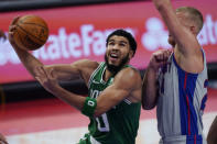 Boston Celtics forward Jayson Tatum (0) makes a layup as Detroit Pistons center Mason Plumlee defends during the first half of an NBA basketball game Friday, Jan. 1, 2021, in Detroit. (AP Photo/Carlos Osorio)