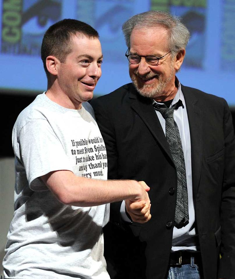"""<a href=""""http://movies.yahoo.com/movie/contributor/1800010823"""">Steve Spielberg</a> shakes hands with a fan during <a href=""""http://movies.yahoo.com/movie/1810091323/info"""">The Adventures of Tintin</a> Comic-Con 2011 panel on July 22, 2011 in San Diego, California."""