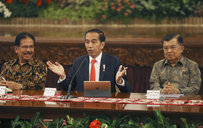 Indonesia President Joko Widodo, center, speaks as his deputy Jusuf Kalla, right, and Minister of Agrarian and Spatial Planning Sofyan Djalil, left, looks on during a press conference at the palace in Jakarta, Indonesia, Monday, Aug. 26, 2019. Indonesia's president has announced to relocate the country's capital from overcrowded, sinking and polluted Jakarta to East Kalimantan province. (AP Photo/Achmad Ibrahim)