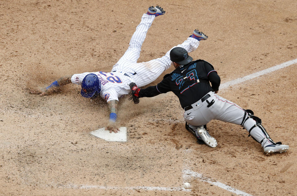 NEW YORK, NEW YORK - AUGUST 31: Javier Baez #23 of the New York Mets slides home with the game winning run in the ninth inning against Alex Jackson #23 of the Miami Marlins at Citi Field on August 31, 2021 in New York City. This is a continuation of the April 11 game which was suspended due to inclement weather. (Photo by Jim McIsaac/Getty Images)