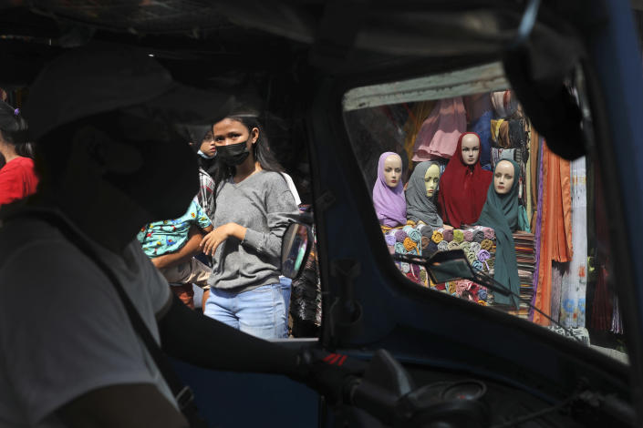 "Mannequins and women wearing masks to curb the spread of coronavirus outbreak are seen through the windows of a three-wheeled motorized taxi called ""bajaj"", during the last week of Ramadan at a market in Jakarta, Indonesia, Tuesday, May 4, 2021. People flock markets and shopping malls in the capital as they shop for food and new clothings in preparation for Eid al Fitr holiday that marks the end of the holiest month in Islamic calendar. (AP Photo/Dita Alangkara)"