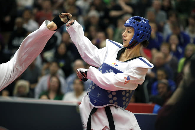 COLORADO SPRINGS, CO - MARCH 10: Diana Lopez backs away from a kick by Danielle Holmquist during the 2012 Taekwondo Olympic Trials at the U.S. Olympic Training Center on March 10, 2012 in Colorado Springs, Colorado. Lopez won the match 3-1. (Photo by Marc Piscotty/Getty Images)