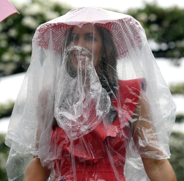 A racegoer arrives during pouring rain before the running of the Melbourne Cup at the Flemington Racecourse in Melbourne, Australia, Tuesday, Nov. 6, 2018. (AP Photo/Andy Brownbill)