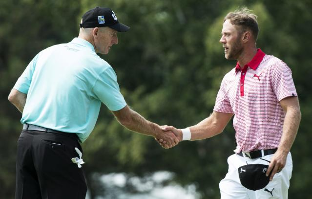 Graham DeLaet, of Canada, right, shakes hands with Jim Furyk following their second round of play at the Canadian Open golf championship Friday, July 25, 2014 in Montreal. (AP Photo/The Canadian Press, Paul Chiasson)