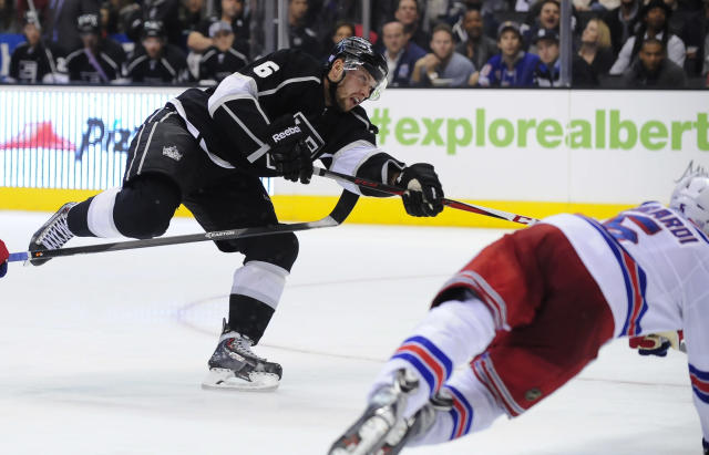 Los Angeles Kings defenseman Jake Muzzin (6) shoots past New York Rangers defenseman Dan Girardi (5) for a goal during the second period of an NHL hockey game, Monday, Oct. 7, 2013, in Los Angeles. (AP Photo/Gus Ruelas)