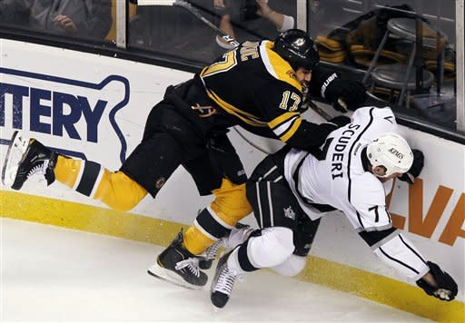 Boston Bruins left wing Milan Lucic (17) checks Los Angeles Kings defenseman Rob Scuderi (7) along the boards in the first period of an NHL hockey game in Boston Tuesday, Dec. 13, 2011. (AP Photo/Elise Amendola)