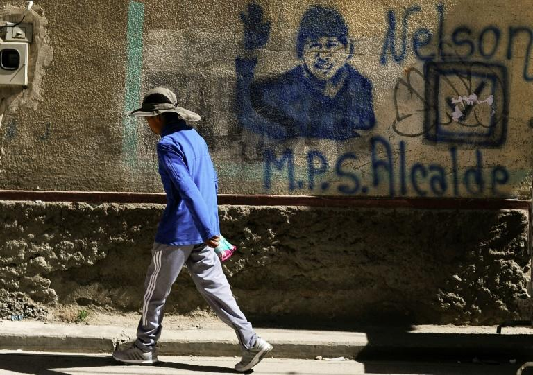 A man walks past of a mural featuring ex-president Evo Morales in Achacachi, Bolivia