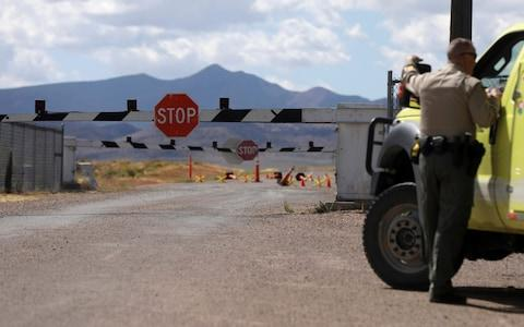 Law enforcement guard the entrance to Area 51 as an influx of tourists responding to a call to 'storm' Area 51 - Credit: Reuters