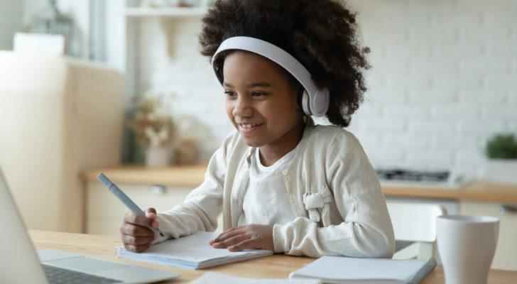 a girl sitting in front of a laptop working on homework. investing for kids
