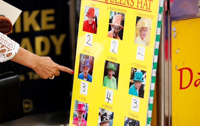 Horse Racing - Royal Ascot - Ascot Racecourse, Ascot, Britain - June 23, 2018 General view of Racegoer pointing at photos of the Queen at Ascot Action Images via Reuters/Andrew Boyers