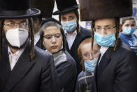 Members of the Orthodox Jewish community gather around a journalist as he conducts an interview on a street corner, Wednesday, Oct. 7, 2020, in the Borough Park neighborhood of the Brooklyn borough of New York. Gov. Andrew Cuomo moved to reinstate restrictions on businesses, houses of worship and schools in and near areas where coronavirus cases are spiking. Many neighborhoods that stand to be affected are home to large enclaves of Orthodox Jews. (AP Photo/John Minchillo)