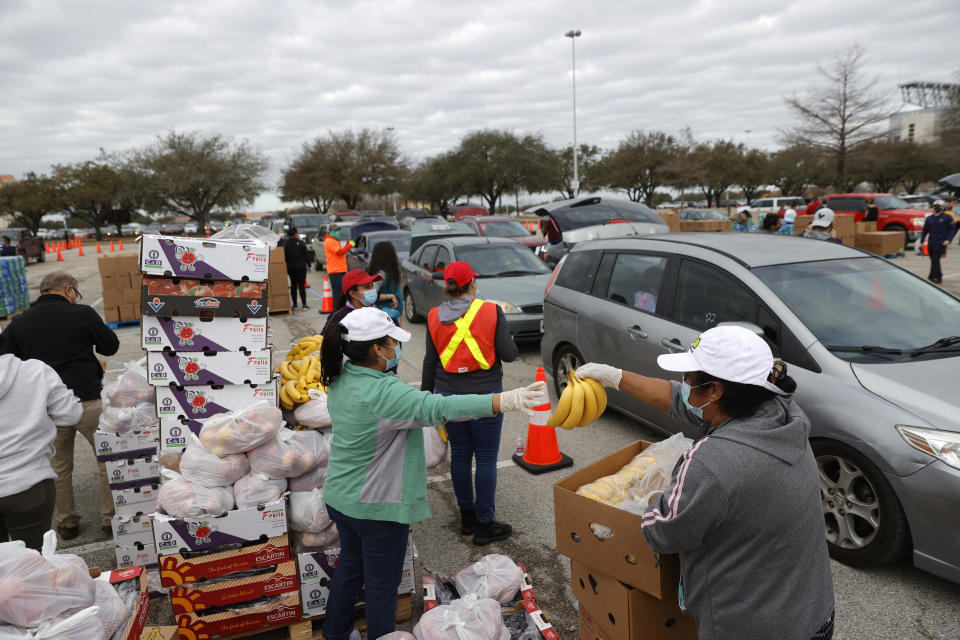 Volunteers prepare to load food into cars during the Houston Food Bank food distribution at NRG Stadium on February 21, 2021 in Houston, Texas. (Photo by Justin Sullivan/Getty Images)