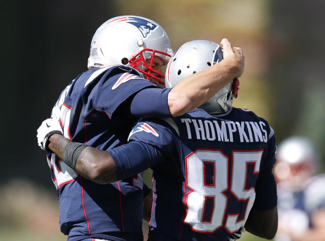 New England Patriots quarterback Tom Brady, left, celebrates his touchdown pass to wide receiver Kenbrell Thompkins (85)in the first half of an NFL football game Sunday, Sept. 22, 2013, in Foxborough, Mass. (AP Photo/Elise Amendola)