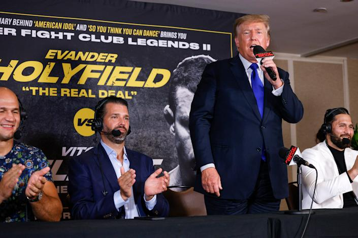 Former President Donald Trump and Donald Trump Jr. speak after the fight between Evander Holyfield and Vitor Belfort.