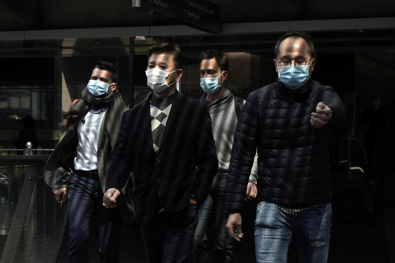 Image: People wearing masks walk in Central, a business district in Hong Kong