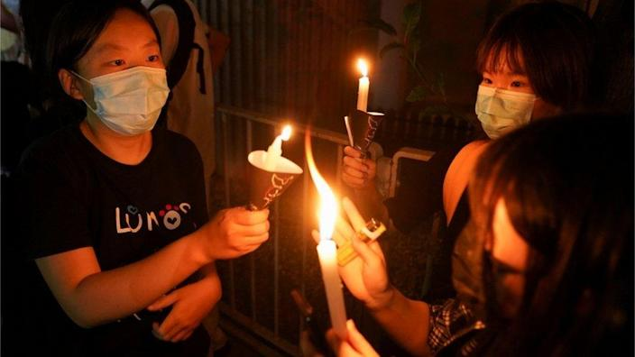 People gathering with candles near Victoria Park in June 2021