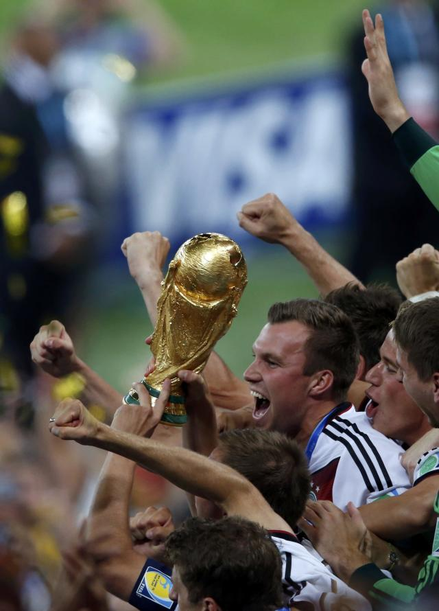 Germany's players lift the World Cup trophy after they beat Argentina in the 2014 World Cup final at the Maracana stadium in Rio de Janeiro July 13, 2014. REUTERS/Paulo Whitaker (BRAZIL - Tags: SOCCER SPORT WORLD CUP)
