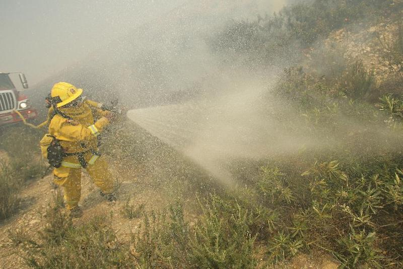 A firefighter sprays down brush as he battles a fire burning in Day Creek near the Etiwanda Preserve in Rancho Cucamonga, Calif., on Wednesday, April 30, 2014. Fire officials say winds gusting to 60 mph are pushing the flames through the foothills of the San Bernardino Mountains east of Los Angeles, although no homes are in immediate danger. Several neighborhoods and at least seven schools in Rancho Cucamonga have been evacuated. There's no word on what sparked the blaze but it comes in the midst of a heat wave that's created extreme fire danger. (AP Photo/The Press-Enterprise, Stan Lim) MAGS OUT; MANDATORY CREDIT