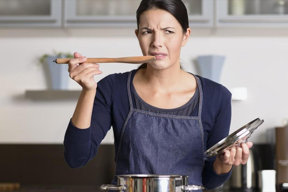 female cook standing at the hob in her apron tasting her food in the saucepan with a grimace as she finds it distasteful and unpalatable